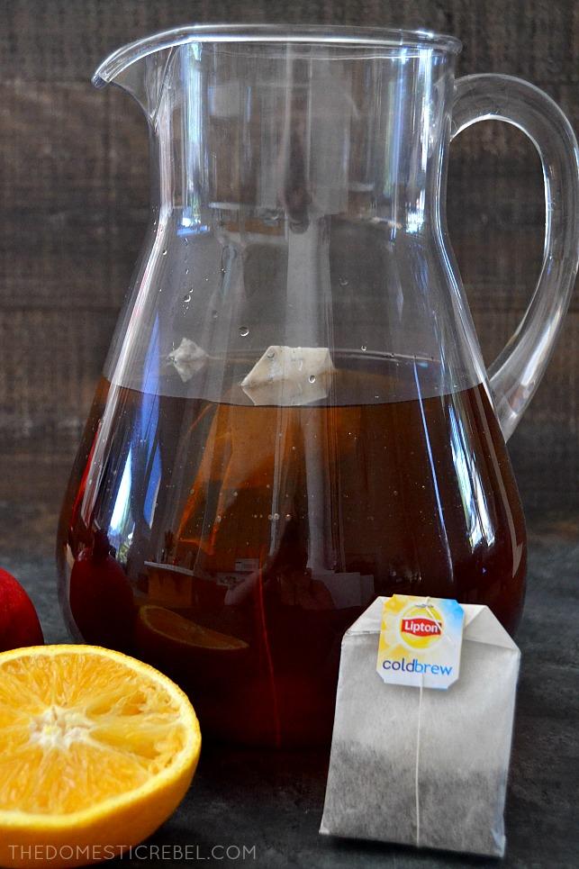 Pitcher of tea with tea bag and orange slice