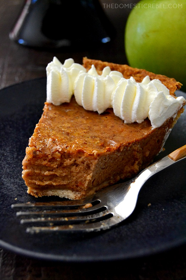 chai apple butter pie slice on black plate with fork and apple in background