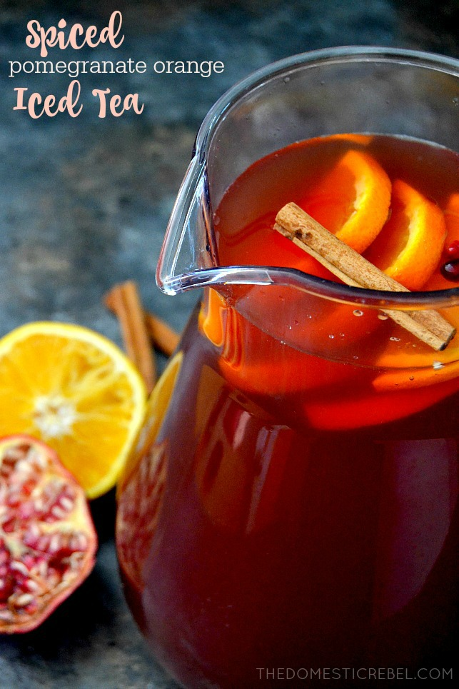 Pomegranate Orange Iced Tea in pitcher with oranges and pomegranates