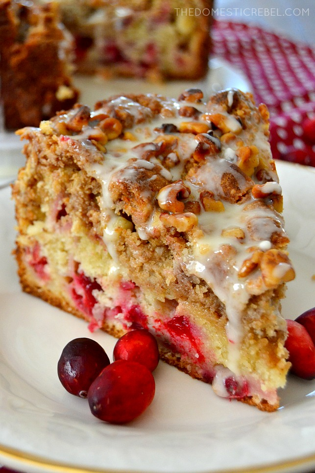 closeup of cranberry walnut crumb cake slice on white plate with cranberries