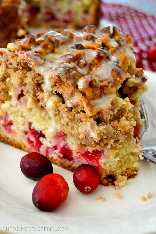 cranberry walnut crumb cake with bite missing on white plate with fork and cranberries