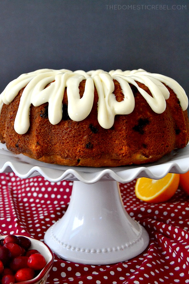 cranberry orange pound cake on white cake stand with cranberries and oranges in background