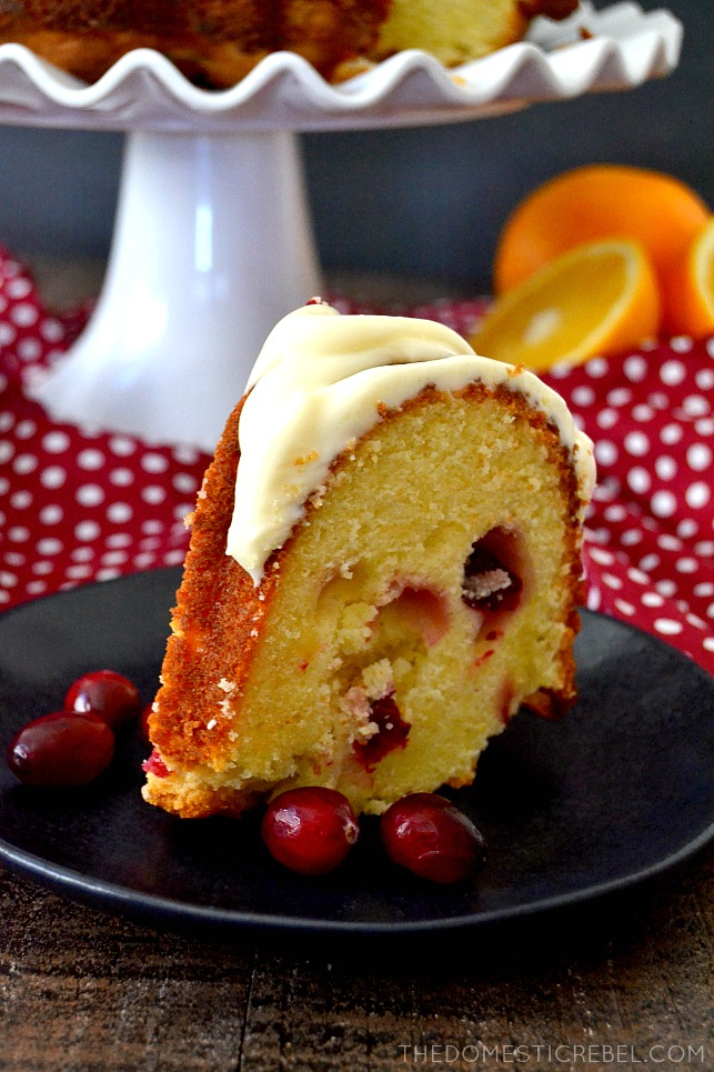 cranberry orange cake slice on black plate with cranberries and oranges