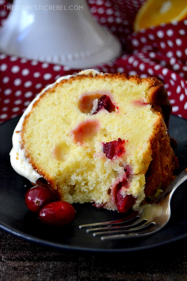 cranberry orange pound cake on black plate with fork and cranberries