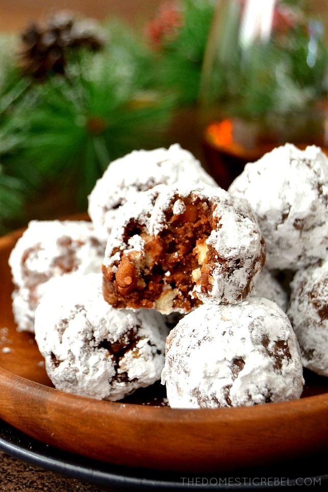 bourbon balls on wooden plate with pine needles in background