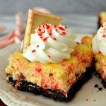 These Peppermint Bark Cheesecake Bars are a winter wonder! Easy, creamy cheesecake bars made with an Oreo cookie crust and topped with a deliciously smooth cheesecake studded with peppermint bark pieces. So fabulous and perfect for Christmas!
