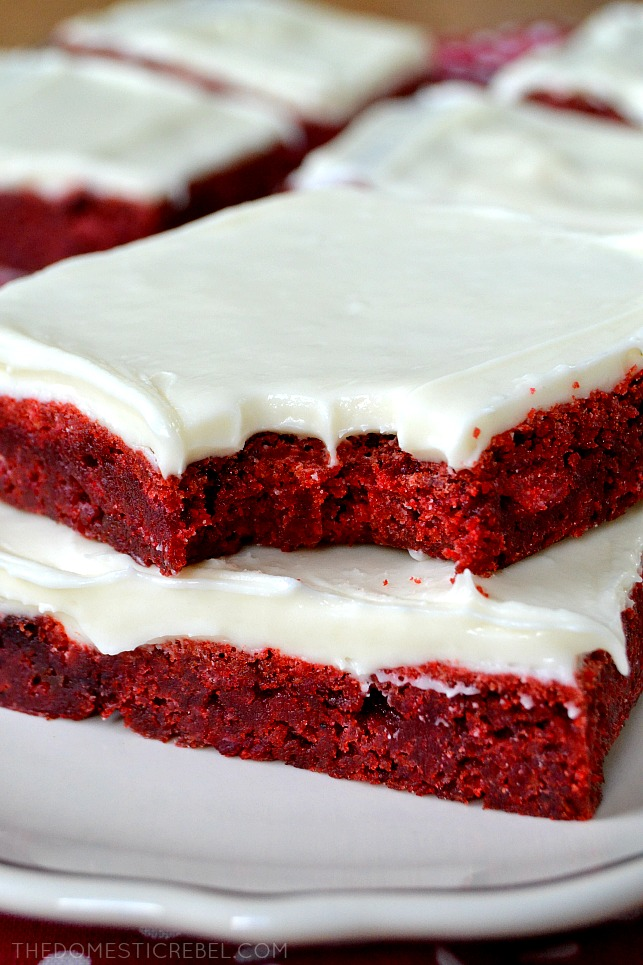 Close up picture of 2 slices of red velvet brownies, one with a bite taken.