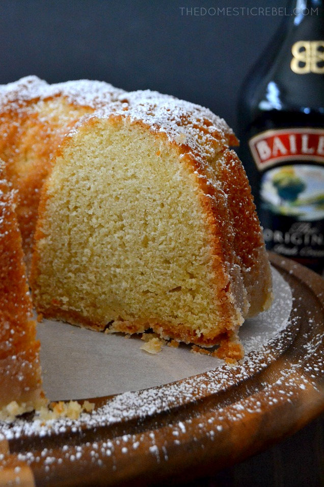 WHOLE CAKE MISSING A SLICE WITH A BAILEY'S BOTTLE IN BACKGROUND.