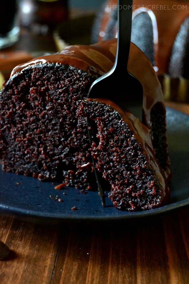 SLICE OF CHOCOLATE CAKE WITH A FORK SLICING A BITE.
