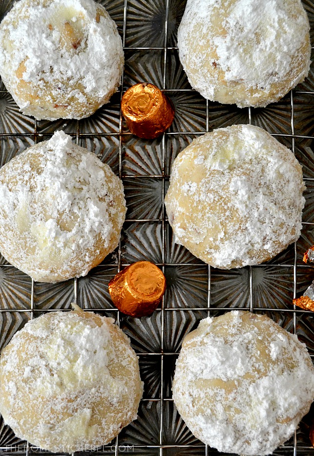SIX SNOWBALL COOKIES ARRANGED IN ROWS ON A COOLING RACK.