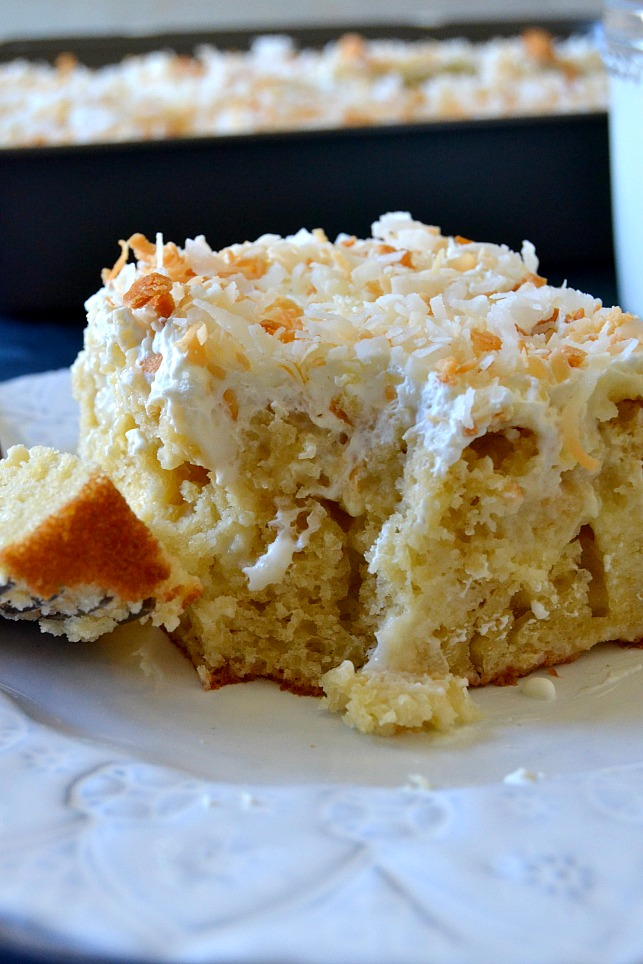 SLICE OF COCONUT POKE CAKE WITH A BITE OF CAKE ON A FORK