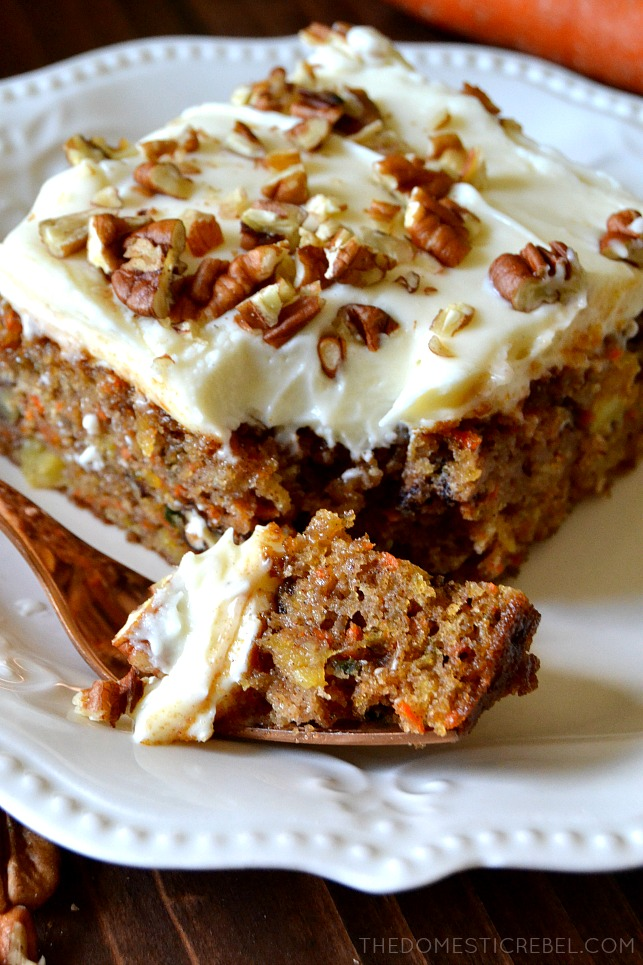 A BITE OF CARROT CAKE ON A FORK IN FRONT OF A SLICE