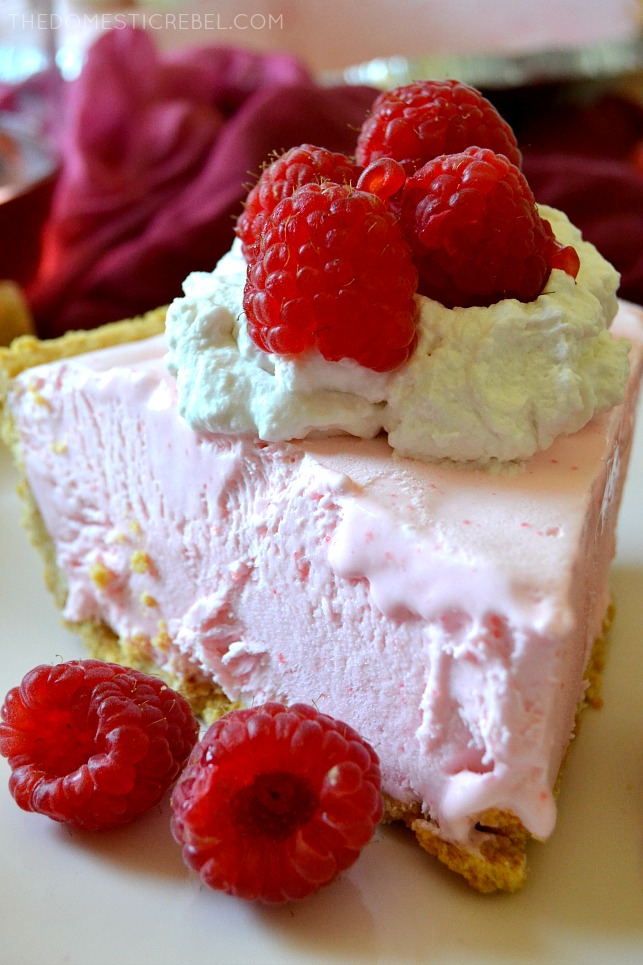 SLICE OF FROZEN ROSE PIE WITH WHIPPED CREAM AND RASPBERRIES