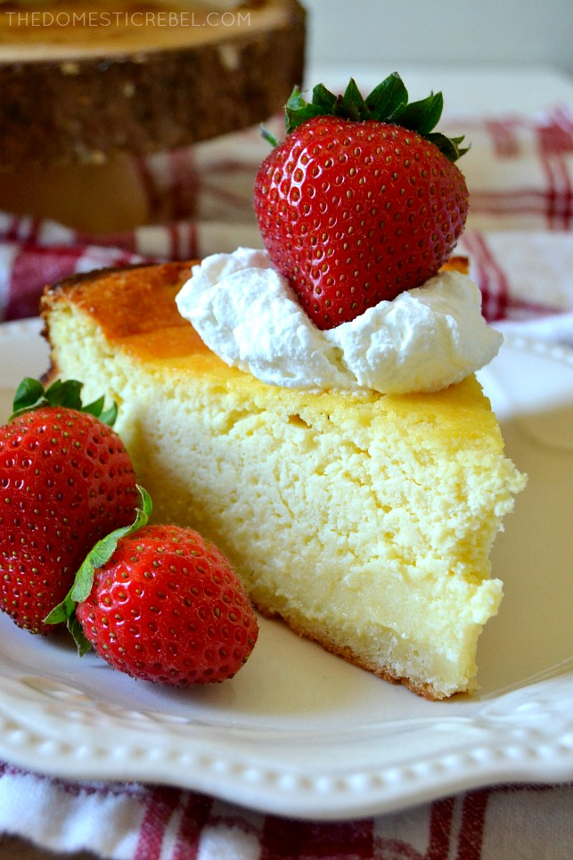 SLICE OF GERMAN CHEESECAKE ON A WHITE PLATE WITH 3 STRAWBERRIES