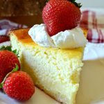 photo of a german cheesecake slice on white plate with strawberries