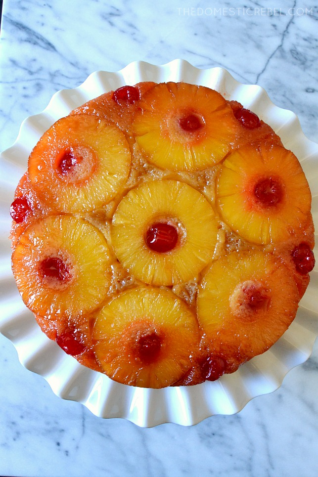 WHOLE UPSIDE DOWN CAKE ON A WHITE CAKE STAND WITH A MARBLE BACKGROUND