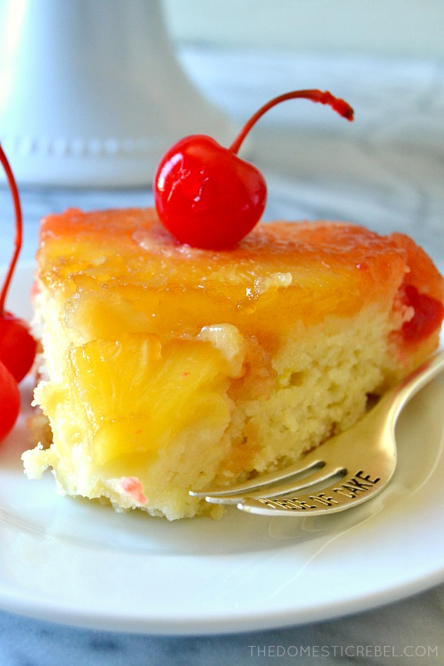 SLICE OF PINEAPPLE UPSIDE DOWN CAKE WITH A CHERRY ON TOP NEXT TO A FORK