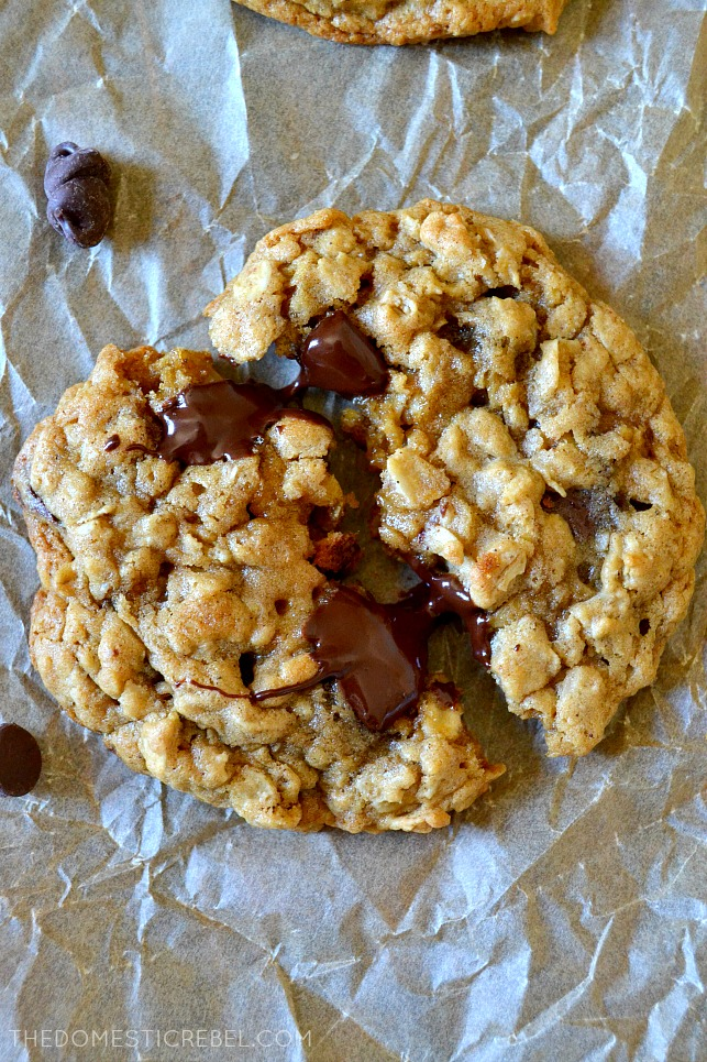 AERIAL VIEW OF OATMEAL CHOCOLATE CHIP COOKIE SPLIT IN HALF ON PARCHMENT