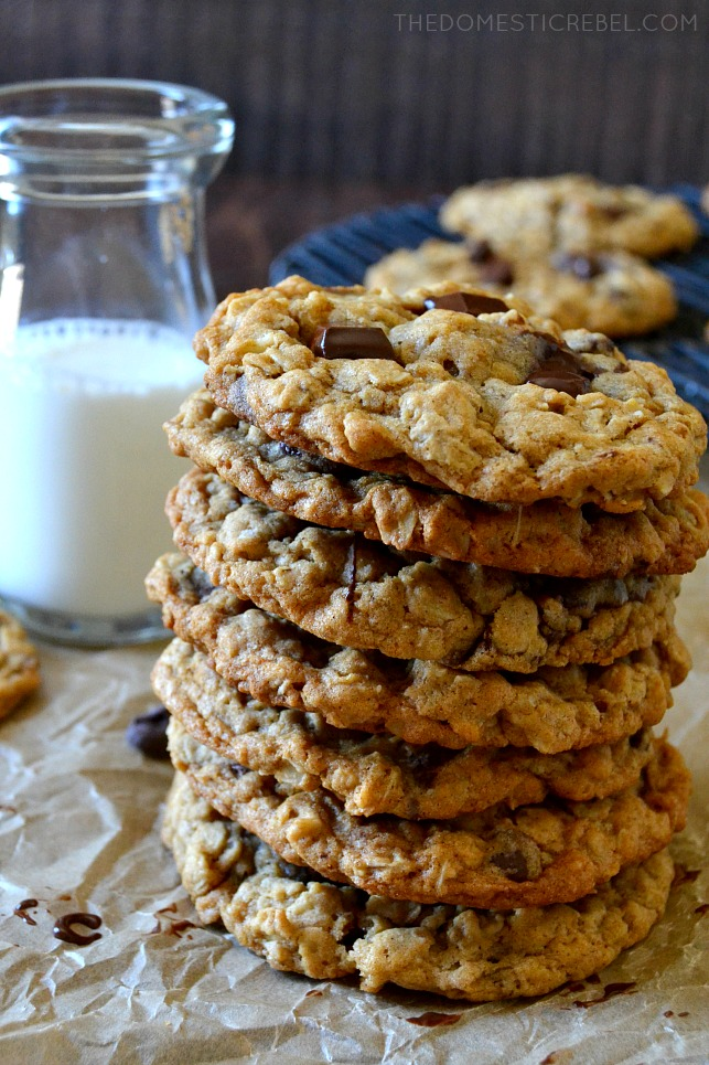 7 OATMEAL CHOCOLATE CHIP COOKIES STACKED WITH GLASS OF MILK IN BACKGROUND