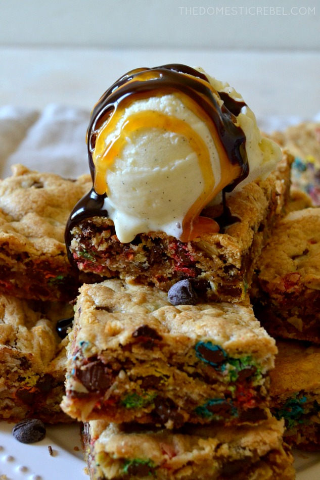 a pile of monster cookie bars with vanilla ice cream and chocolate and caramel drizzle