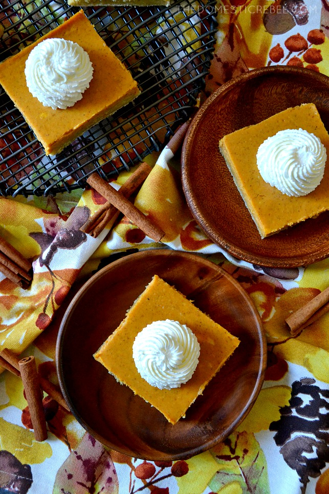two pumpkin cheesecake bars on wooden dishes and one bar on a cooling rack