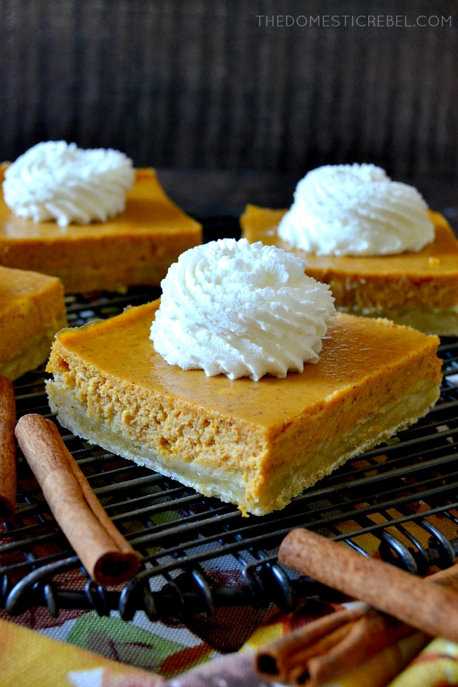 pumpkin cheesecake bar squares arranged on a cooling rack
