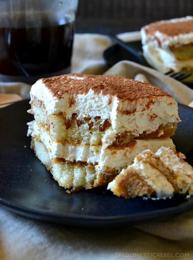 slice of tiramisu with a bite missing on a navy plate