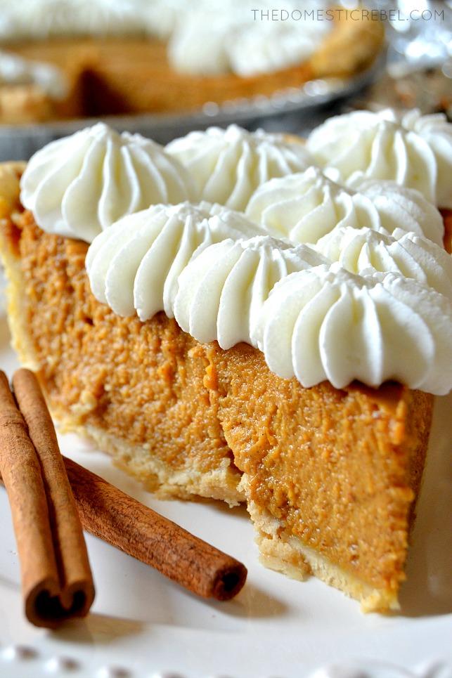 slice of pumpkin pie next to two cinnamon sticks