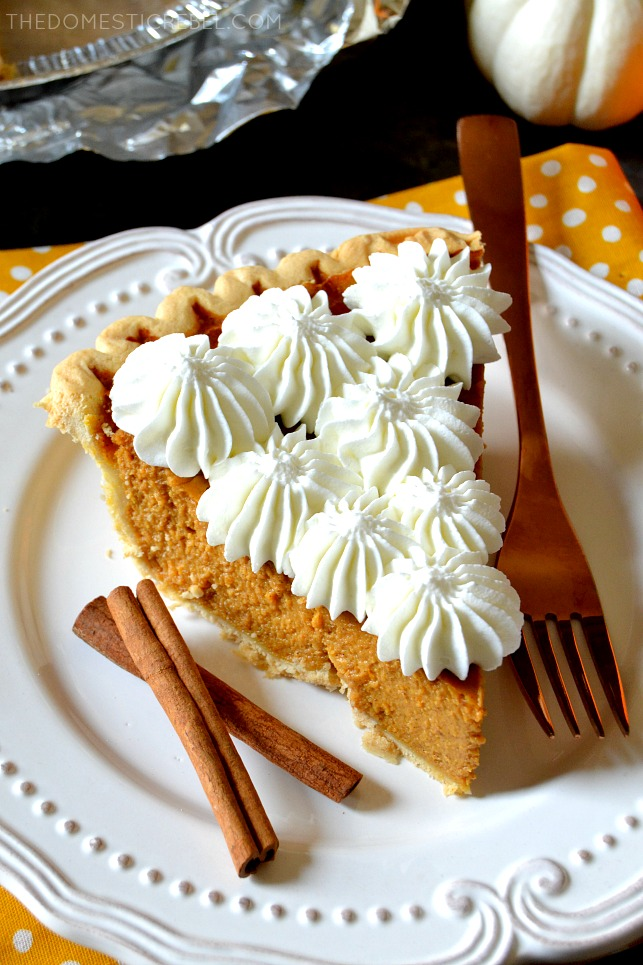aerial view of slice of pumpkin pie on a white plate next to a fork