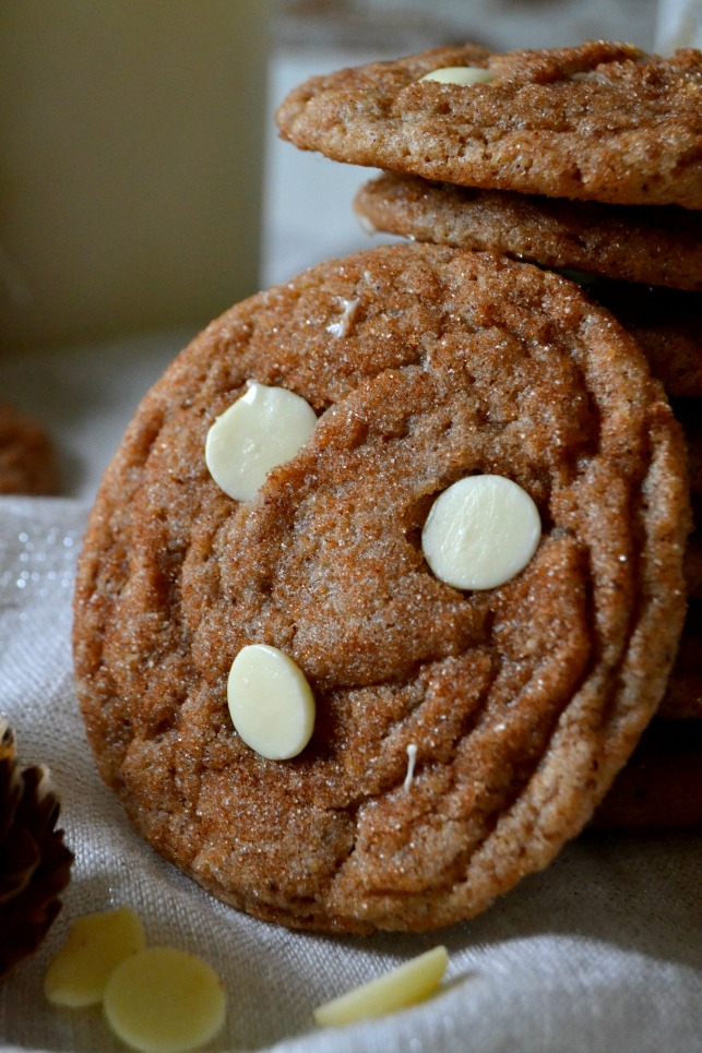 close up of snickerdoodle propped up against a stack of cookies