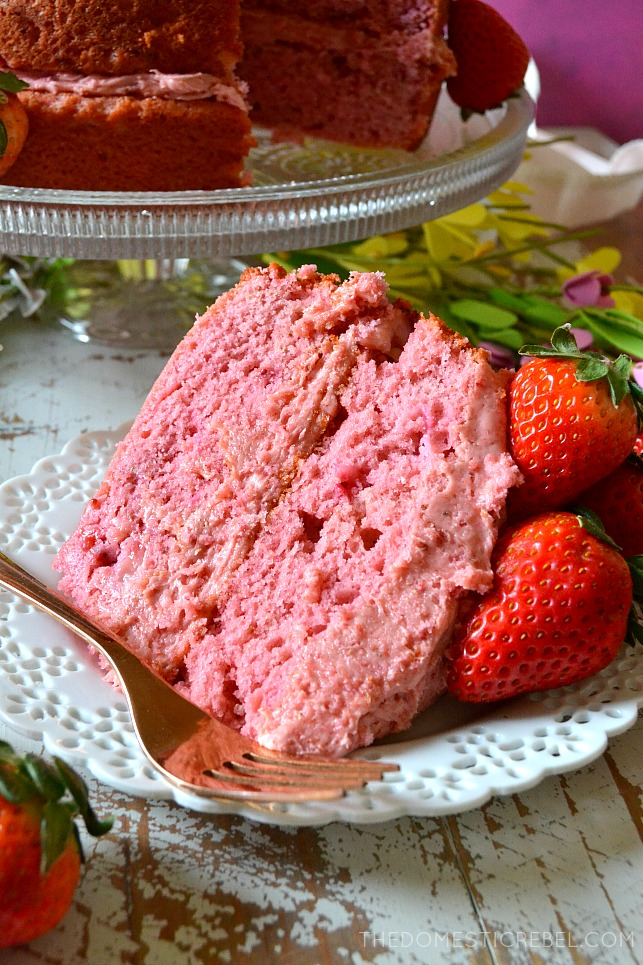 slice of strawberry cake on a white plate with whole strawberries