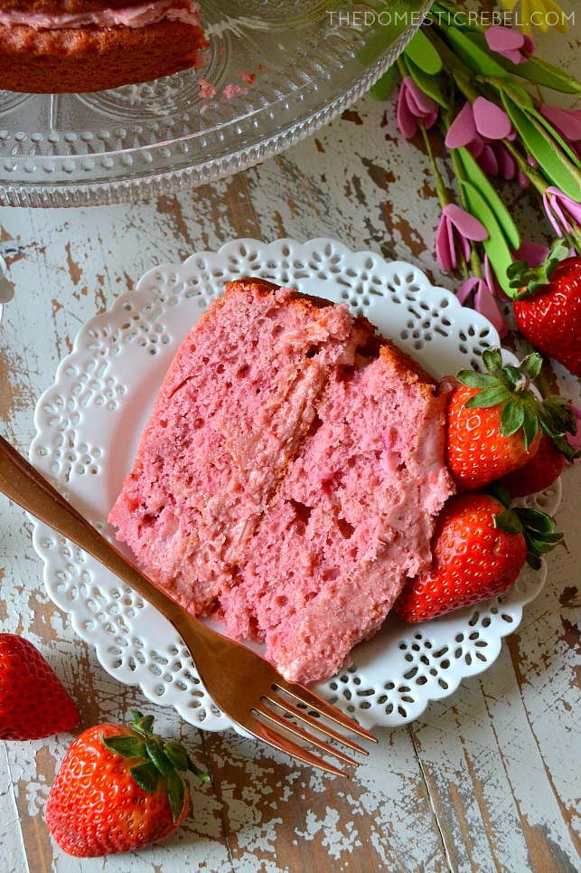 slice of strawberry cake on a white plate next to a fork