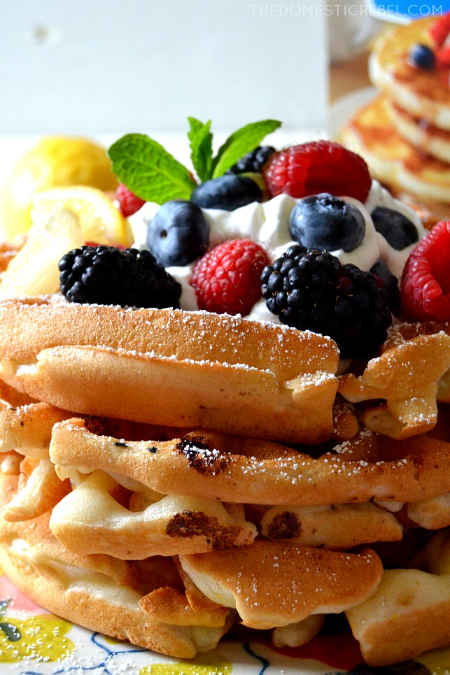 close up of stacked waffles with powdered sugar on them