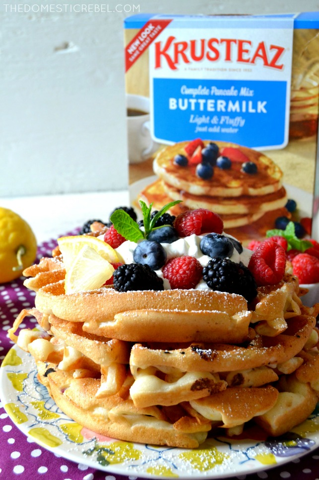 four triple berry lemon waffles stacked in front of a box of Krusteaz buttermilk pancake mix