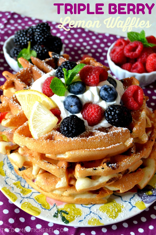 four triple berry waffles stacked on a patterned plate