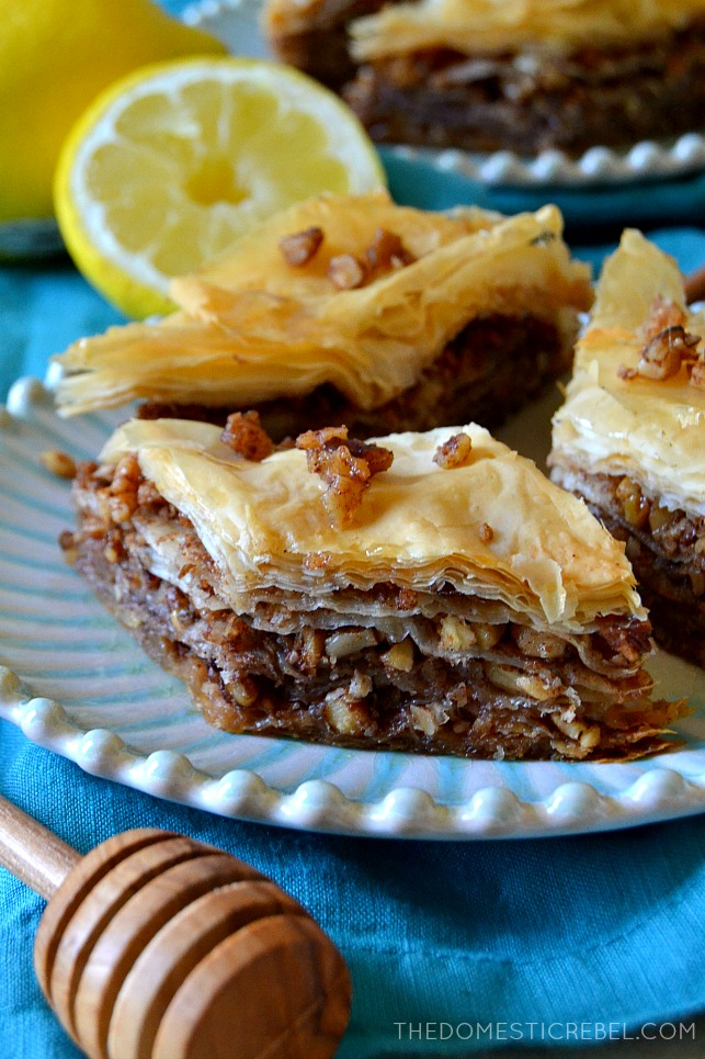 three pieces of baklava next to a honey dipper