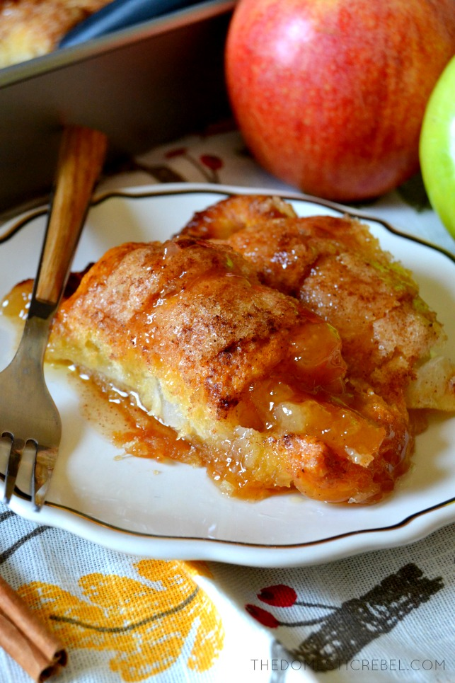 Two apple dumplings on a white plate with a fork.