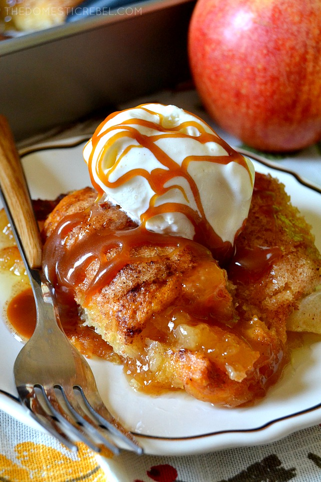 Apple dumplings on a white plate topped with vanilla ice cream and caramel