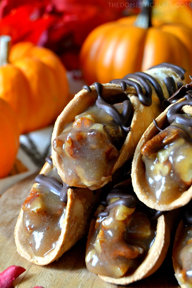 Four pecan pie cannolis stacked in front of faux pumpkins