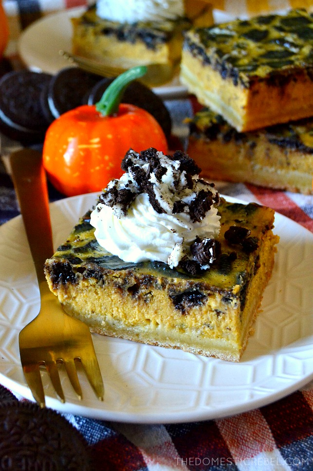 An Oreo pumpkin cheesecake bar square topped with whipped cream and crushed Oreos
