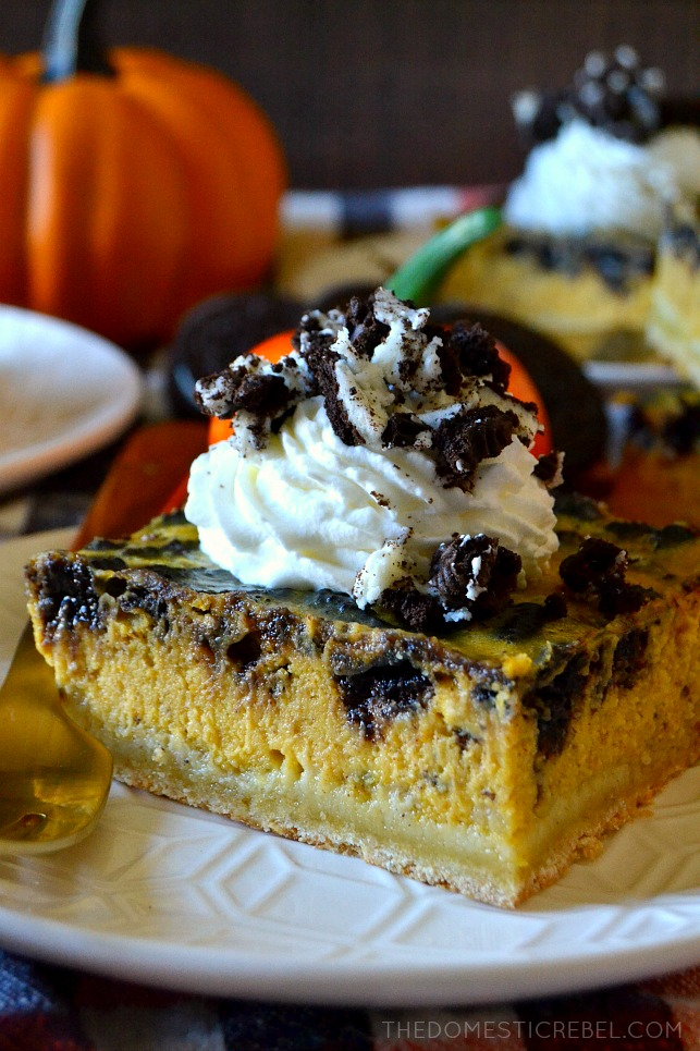 Close up of an Oreo pumpkin cheesecake bar on a textured white plate