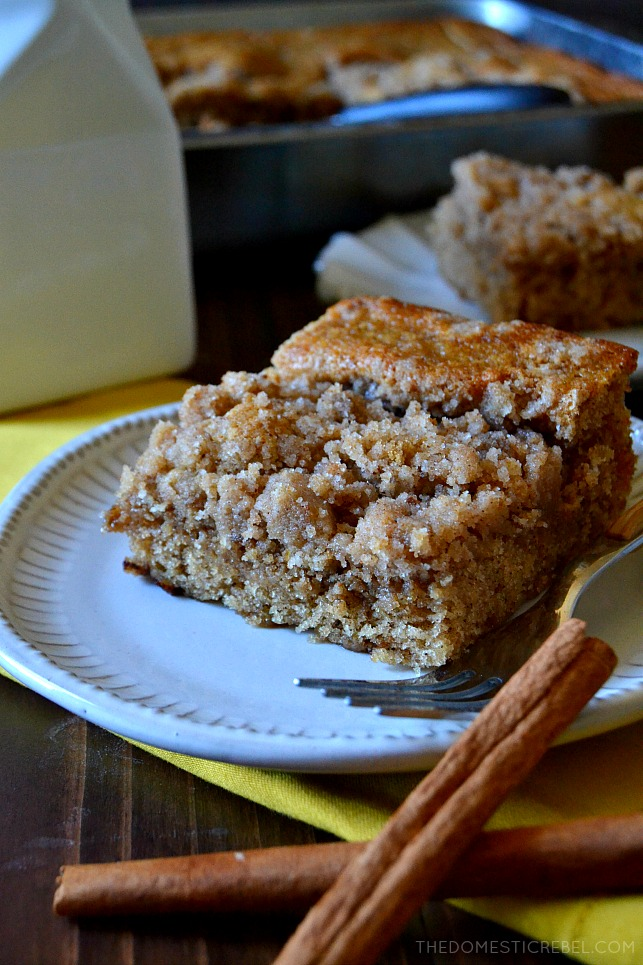 Slice of coffee cake on a plate next to two cinnamon sticks