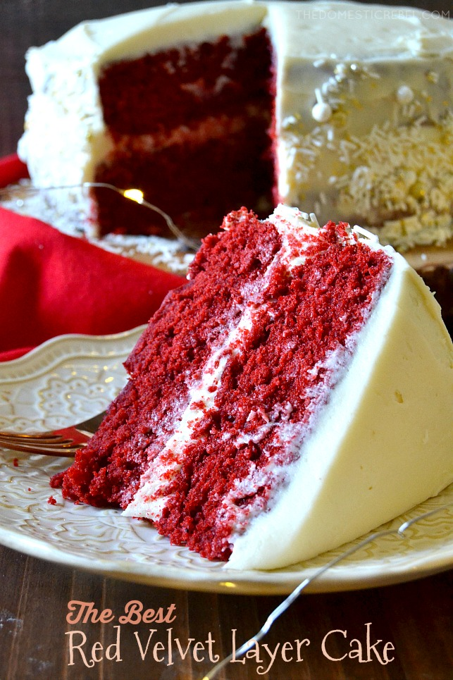 Slice of red velvet layer cake on its side on a white plate