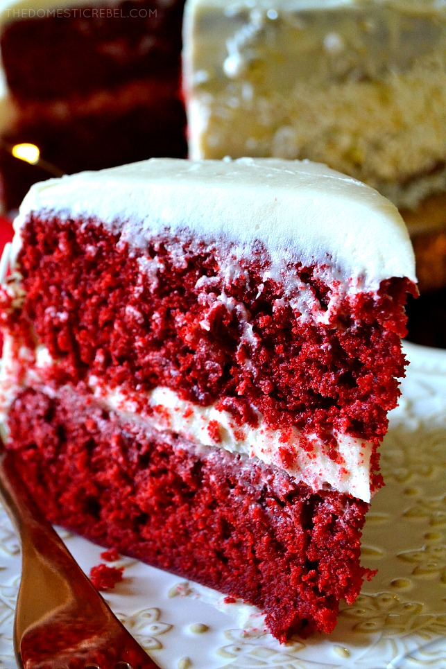 Slice of red velvet layer cake standing upright on a white plate