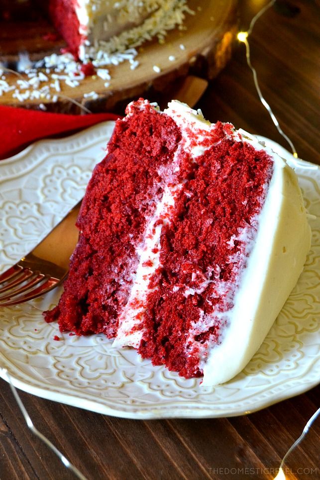 Aerial view of a slice of red velvet layer cake on a white plate with a copper fork