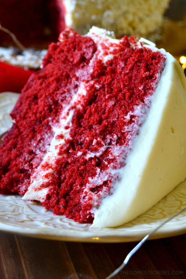Slice of red velvet layer cake on an ornate white plate