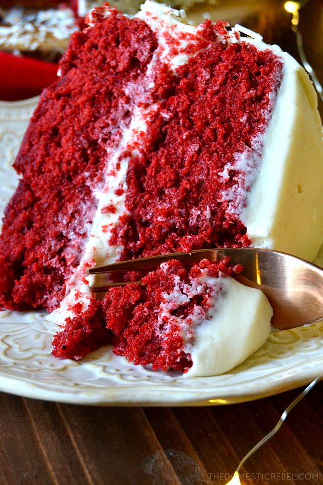 A fork slicing into a slice of red velvet layer cake
