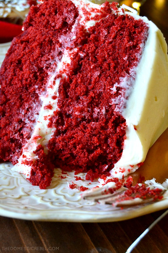 Close up of a red velvet layer cake slice missing a bite from the top layer