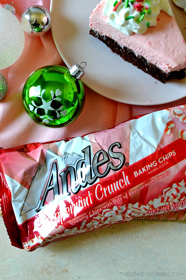 A bag of Andes Peppermint Crunch Baking Chips next to a slice of peppermint brownie cheesecake