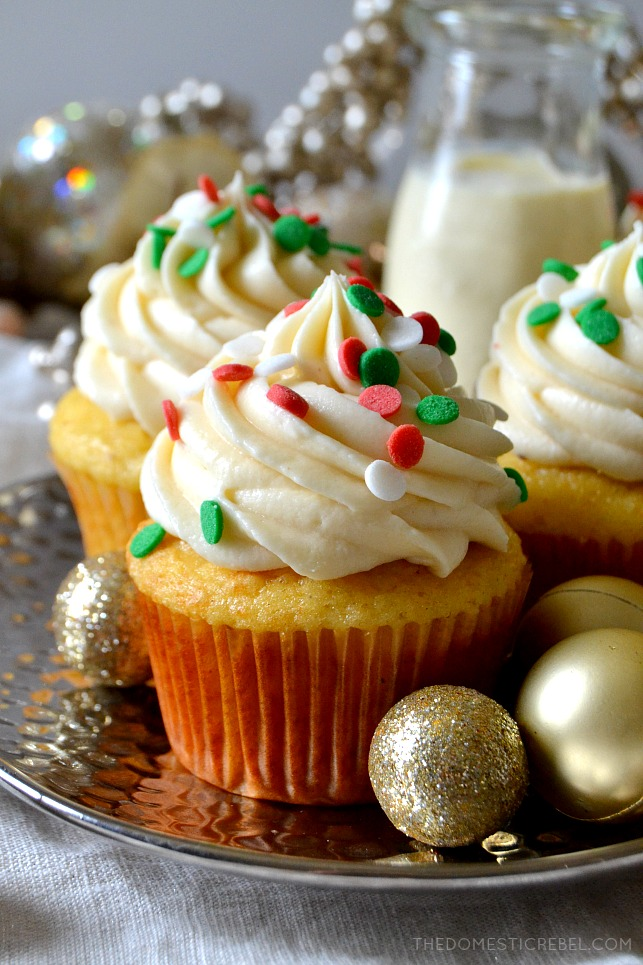 Close up of one eggnog cupcake topped with red and green sprinkles